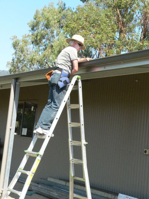 Doug Hamilton placiing the leave stopper in the guttering.